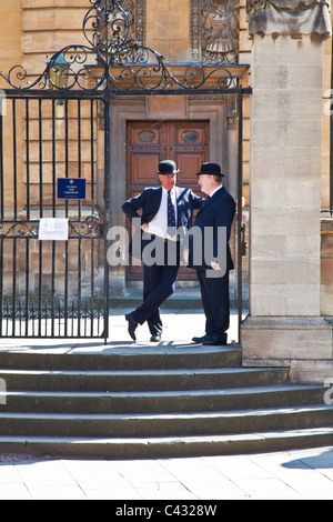 Two Oxford 'Bulldogs' in traditional bowler hats outside Sheldonian Theatre, Oxford University, Oxford, England, - Stock Photo