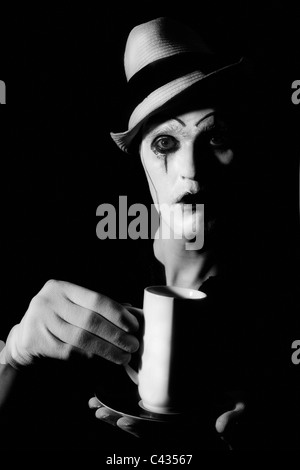 Portrait of terrible mime clown holding white cup - Stock Photo