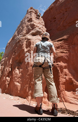 A rock-climbing student watches as her guide scales one of the Sentinel Spires in Garden of the Gods Park, Colorado Springs, CO