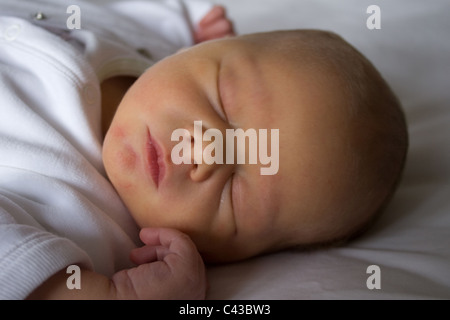 Four day old baby with a touch of jaundice sound asleep at home - Stock Photo