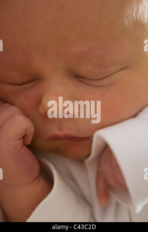 Scrunched up little 4 day old baby boy - asleep at home - Stock Photo