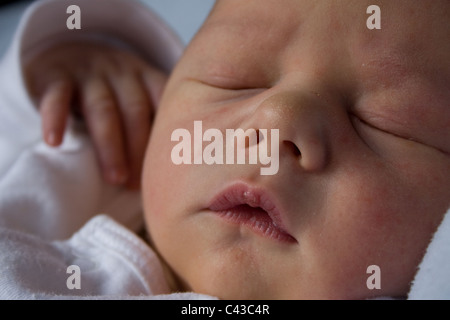 4 day old baby sleeps peacefully at home, with hand poised in the air - Stock Photo