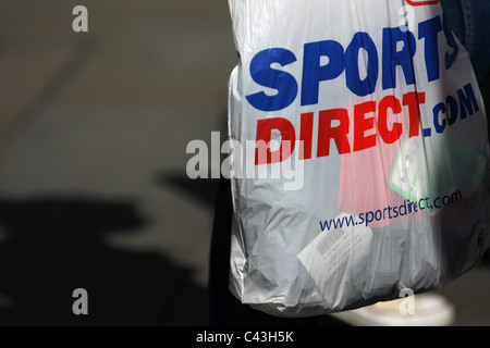 04fc39416029 Trolly travel bag  A Sport Direct plastic shopping bag being carried in  London - Stock Photo