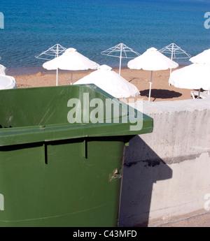 GREEN RUBBISH BIN BESIDE AN EMPTY BEACH IN GREECE - Stock Photo