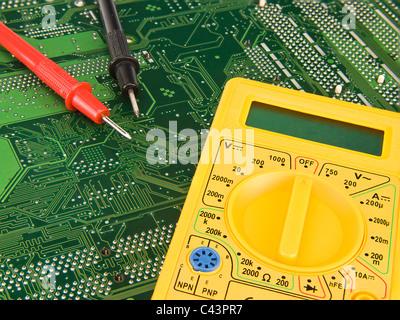 Yellow multimeter on green printed circuit board - Stock Photo