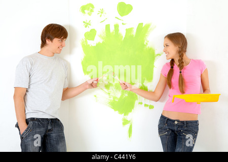 Affectionate couple holding paintbrushes while looking at each other with painted wall on background - Stock Photo