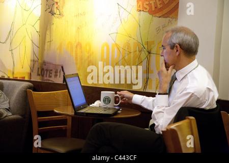 A businessman working on his laptop in Starbucks Coffee bar, Membury Motorway services, M4, Wiltshire, UK