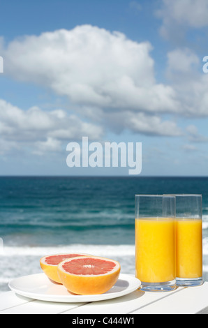 Orange juice and grapefruit by the ocean - Stock Photo