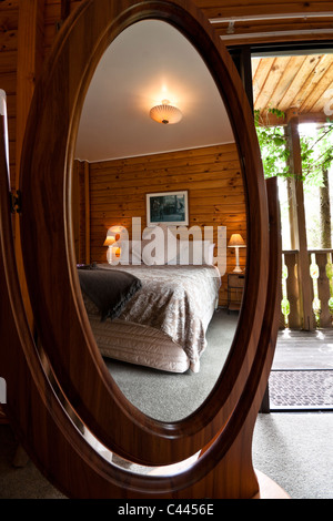 Nice warm bedroom interior of mountain lodge reflected in mirror. - Stock Photo