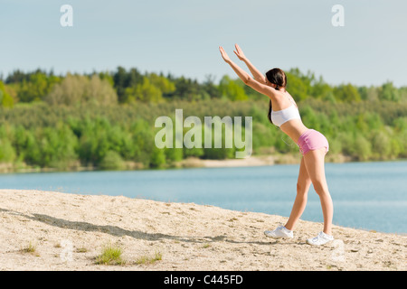 Summer active woman stretching on beach in fitness outfit - Stock Photo