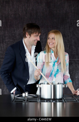 Couple cooking and looking happy. - Stock Photo