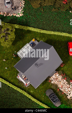A diorama of miniature cars, people and a house, directly above - Stock Photo