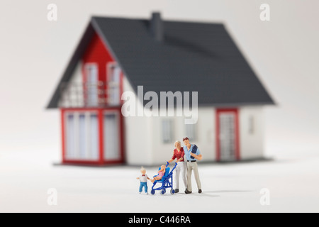 A young family of miniature figurines in front of a house - Stock Photo
