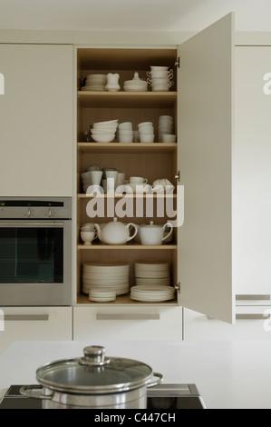 Open crockery cupboard in white contemporary kitchen - Stock Photo