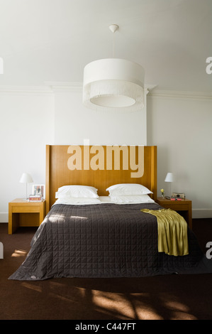 Double bed with wooden headboard and quilt in white bedroom with large light shade - Stock Photo