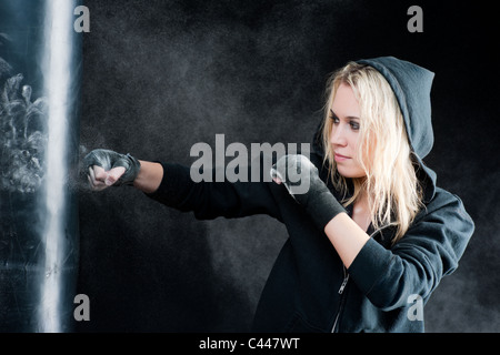 Blond boxing woman in black training with punching bag - Stock Photo