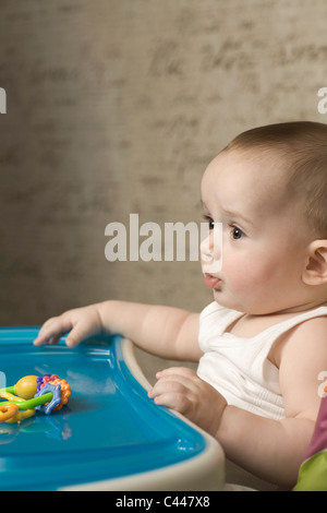 A baby in a high chair patiently waiting for food - Stock Photo