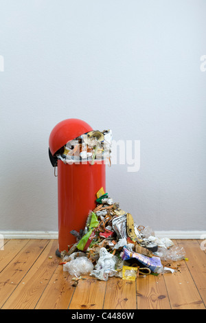 An overflowing garbage can of rotting food and recyclables - Stock Photo