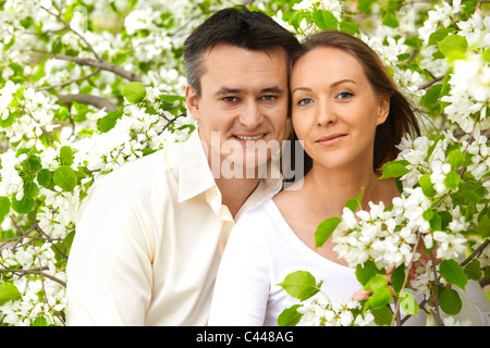 Portrait of young couple looking at camera among apple trees - Stock Photo