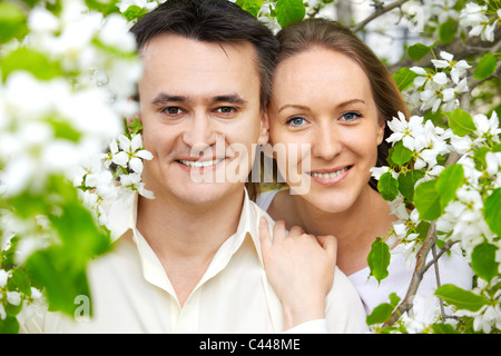 Portrait of young couple looking at camera among apple blossom - Stock Photo