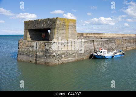 Sea wall and fishing boat at Craster, Northumberland - Stock Photo