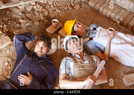 Three construction workers taking a coffee break - Stock Photo