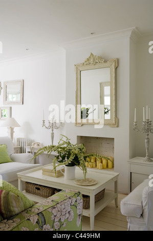White living room with coffee table, mirror and floral patterned sofa. - Stock Photo