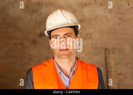 A well-dressed man wearing a hardhat and reflective vest at a building site - Stock Photo