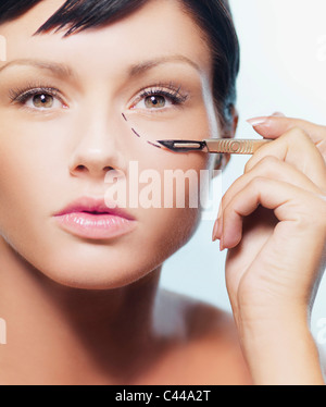 A woman with a dotted line under her eye holding a scalpel - Stock Photo