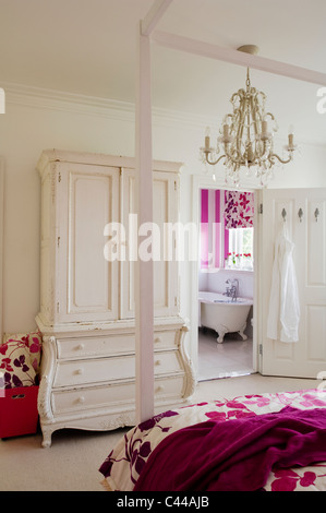 Fourposter bed in bedroom with white wardrobe with drawers, chandelier and en suite - Stock Photo