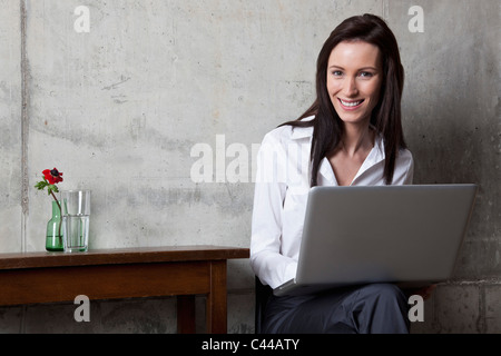 A businesswoman with a laptop smiling at the camera - Stock Photo