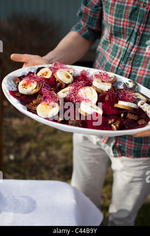Man holding a serving dish of goat's cheese - Stock Photo