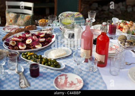 Dining table outside with crockery  and food such as olives and goat's cheese - Stock Photo