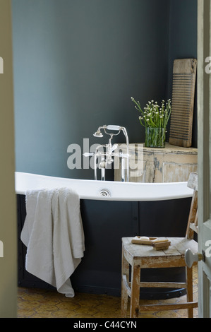 Eiffel freestanding bath in bathroom with distressed salvage style wooden french furniture - Stock Photo