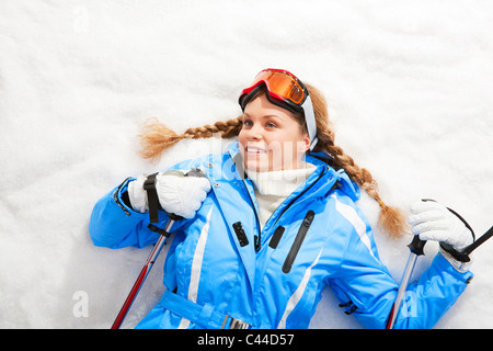 Portrait of teenager holding skiing sticks and lying on snow - Stock Photo