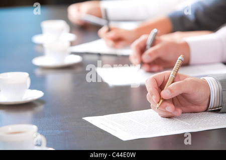 Close-up of masculine hand holding ballpoint over business document on background of human hands with cups of coffee - Stock Photo