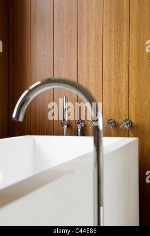 Corian bathtub with taps set in to the wall panelling - Stock Photo