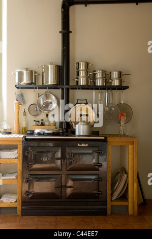 Country style kitchen with aga and saucepans on open shelving - Stock Photo