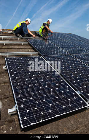 Fitting solar pv photovoltaic panels to house roof Llanfoist Wales UK - Stock Photo