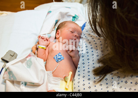 Mother with Newborn Baby Boy in Hospital immediately after Birth - Stock Photo