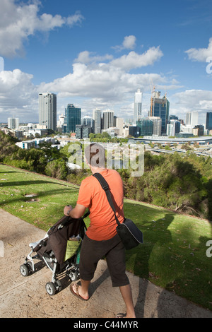 Man pushing stroller with view of city skyline from Kings Park. Perth, Western Australia, Australia - Stock Photo