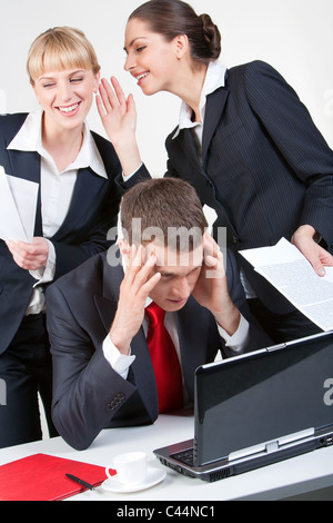 Photo of thinking boss in front of laptop while one of his employees whispering something to another woman - Stock Photo