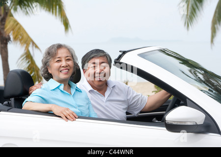 Happy Senior Couple Posing in a Convertible - Stock Photo