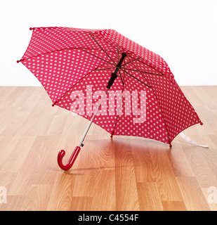 Open red and white spotted umbrella on floor, close-up - Stock Photo