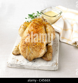 Roasted chicken on chopping board, close-up - Stock Photo