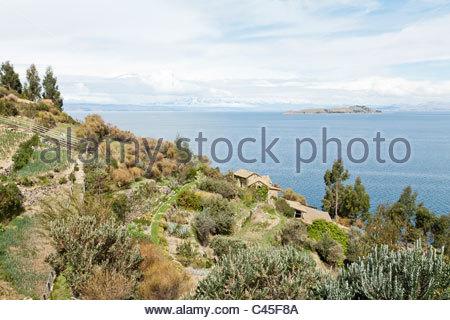 View of small farm on Isla del Sol with Isla de la Luna, the Cordillera Real and Lake Titicaca in background. - Stock Photo