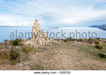 Stone cairn with Cordillera Real and Isla de la Luna in background. Isla del Sol, Lake Titicaca, La Paz Department, - Stock Photo