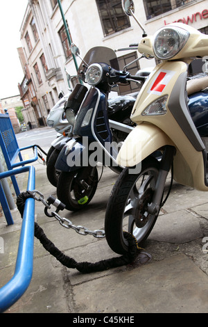 A parked scooter securely chained on a U.K. street. - Stock Photo