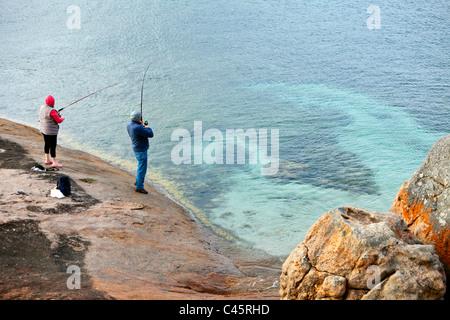 Couple fishing off rocks at Lucky Bay. Cape Le Grand National Park, Esperance, Western Australia, Australia - Stock Photo