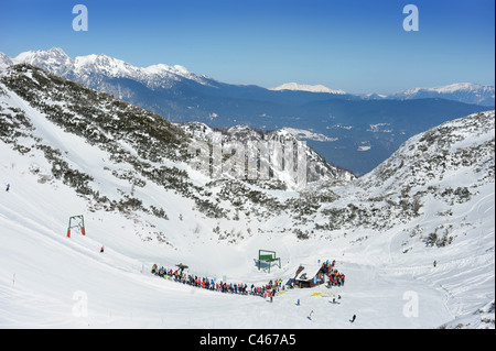 Skiers queue for a chairlift at the Vogel Ski Centre on the base of the Kratki plaz and Konta pistes in the Triglav - Stock Photo